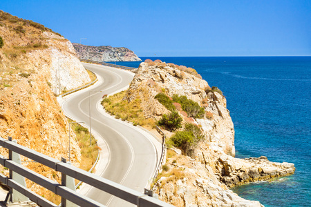 Mountain roads and serpentines of Crete, cars move along the winding highway along the sea shore, Heraklion, Crete, Greece