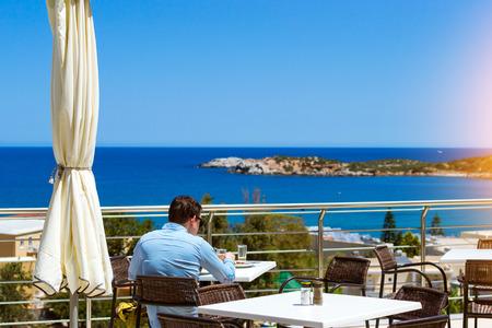 4 star: Young man in blue shirt is having lunch on veranda of restaurant, overlooking the Cretan sea. Resort hotel Atali Village 4 star, Bali, Rethymno, Crete, Greece