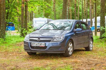 suomi: HAMINA, FINLAND - JUNE 13, 2014: Summer outdoor recreation, Scandinavian vacation. Car Opel Astra H parked in a wooded campsite among pine trees. Finnish Gulf. Area for camp in woods. Hamina, Finland, Suomi