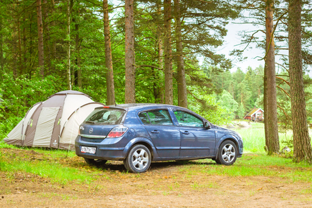 HAMINA, FINLAND - JUNE 13, 2014: Summer outdoor recreation, Scandinavian vacation. Car Opel Astra H parked in a wooded campsite among pine trees. Finnish Gulf. Area for camp in woods.