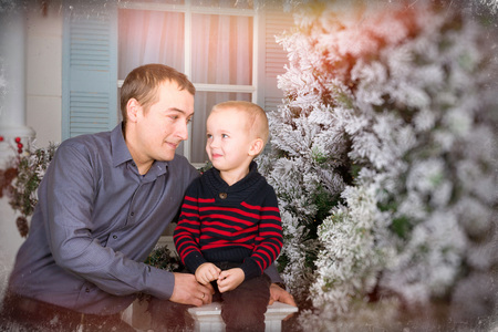 photo shoot: Caring father with his son posing for a joint portrait. June 19 - an international holiday Fathers day. Family photo shoot in bright new year interiors Stock Photo