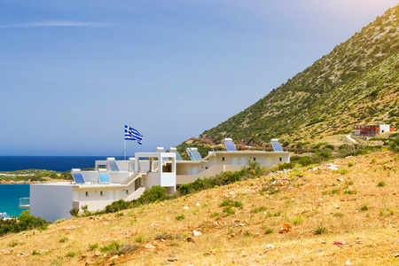 Modern Greek architecture - new white building in constructivist style, stands on shore of Cretan sea on roof mounted solar panels with hot water heaters, on flagpole the flag of Greece. Resort village Bali, Rethymno, Crete, Greece Stock Photo