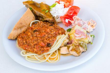 rethymno: Spaghetti Bolognese with a Greek salad on a white plate. Bali, Rethymno, Crete, Greece