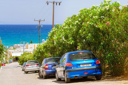 sloping: BALI, GREECE - APRIL 29, 2016: Rental car Peugeot 206 are parked on the sloping street leading to the sea, about office leasing transport. Resort village Bali, Rethymno, Crete, Greece Editorial