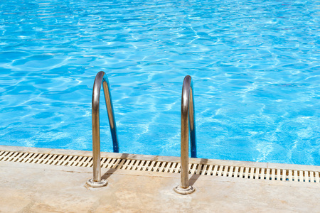Metal hand railing of staircase to public swimming pool with clear blue water. Bali, Rethymno, Crete, Greece