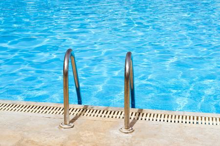 Metalen hand railing van de trap naar openbaar zwembad met helder blauw water. Bali, Rethymno, Kreta, Griekenland Stockfoto