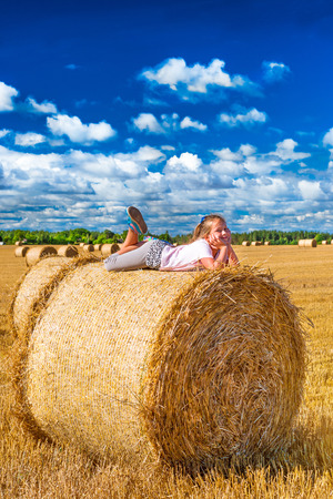 cute young farm girl: Cute young girl having fun on haystack. Stacks of straw - bales of hay, rolled into stacks left after harvesting of wheat ears, agricultural farm field with gathered crops rural. Pargi, Voka, Estonia Stock Photo