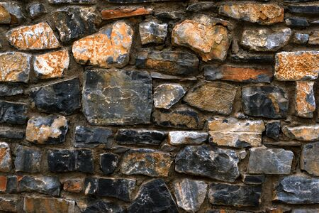 granite wall: Stone texture of granite wall for the background. Dark monolithic stones joined with cement in a single stone panel. Greek architecture, Bali, Crete Stock Photo