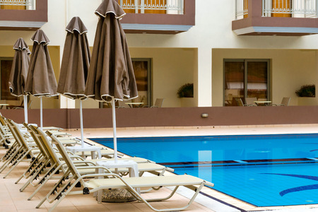 hotel resort: BALI, GREECE - APRIL 29, 2016: Empty sunbeds and umbrellas are at the pool empty without tourists early in morning. Relax and sunbathe by pool with clear blue water in Resort hotel Bali, Crete, Greece