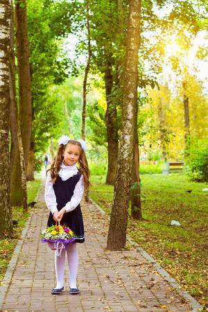 žák: Malý first-srovnávač, dívka žák chodí do školy v den poznání - prvního září. Žák základní školy v uniformě s luky pózuje v podzimní krajinu, pletenec ramenní tašku s učebnicemi. Rusko Reklamní fotografie