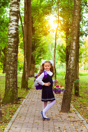 Little first-grader, girl-student goes to school on knowledge day - September First. Student of elementary school in uniform with bows posing in autumn landscape, shoulders bag with textbooks. Russia