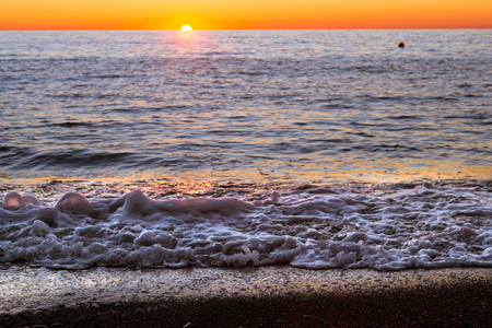rushes: Foam sea wave rushes at pebble seashore, shore of beach is covered in glittering sun stones. Bright sunset on the Black sea coast. Sochi, Krasnodarskiy kray, Russia Stock Photo