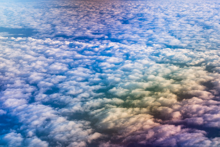 long distance: Airplane flying above cumulus clouds. View of sky from aircraft, long distance travel by airtransport. Russian airlines Stock Photo