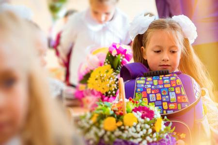 žák: Malý first-srovnávač, dívka žák chodí do školy v den poznání - prvního září. Žák základní školy v uniformě s luky, představující v učebně pro studentské Desk, pletenec ramenní tašku s učebnicemi. Rusko Reklamní fotografie