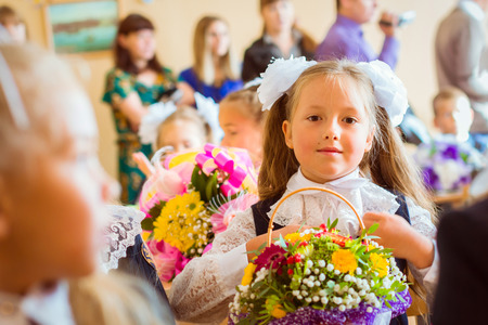 Little first-grader, girl-student goes to school on knowledge day - September First. Student of elementary school in uniform with bows posing in classroom for student Desk, shoulders bag with textbooks. Russia
