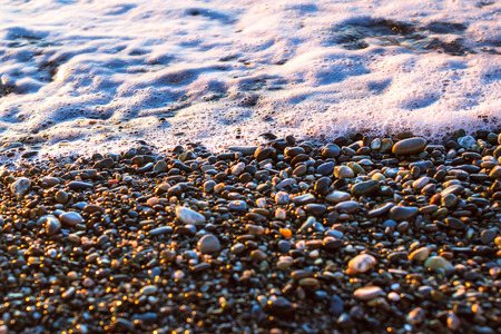 rushes: Foam sea wave rushes at pebble seashore, shore of beach is covered in glittering sun stones. Stone background with texture of pebbles. Sochi, Krasnodarskiy kray, Russia Stock Photo