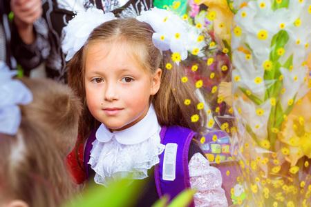 žák: Malý prvotřídní student, studentka, chodí do školy v den znalostí - první září. Student ze základní školy v uniformě s luky představující, rameno taška s učebnicemi. Rusko