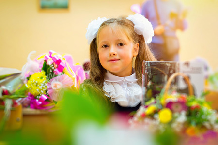 first year student: Little first-grader, girl-student goes to school on knowledge day - September First. Student of elementary school in uniform with bows posing in classroom for student Desk, shoulders bag with textbooks. Russia