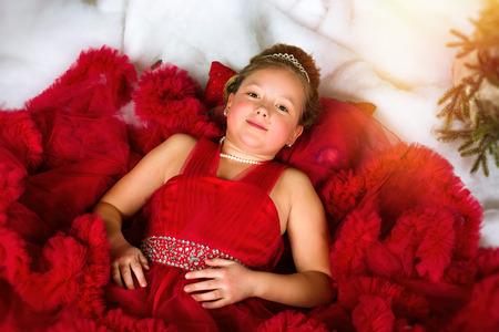 corona navidad: La pequeña princesa de invierno en una corona preciosa en el vestido rojo se encuentra en la nieve artificial. Se felicita por Año Nuevo y la Navidad en el interior encantador de fiesta con el árbol de Navidad Foto de archivo