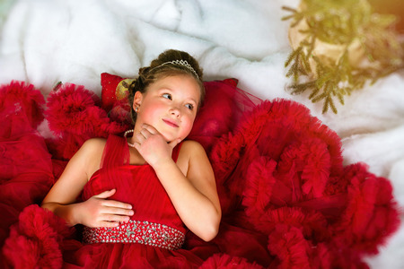 corona navidad: Little winter Princess in a precious crown in red dress lies on artificial snow. Welcomes New year and Christmas in enchanting holiday interior with Christmas tree