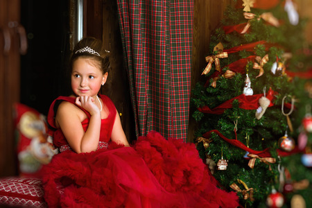Little winter Princess - girl in red dress, sitting on windowsill, looks out window at night. Celebration of New year and Christmas in enchanting holiday interior with decorated pine