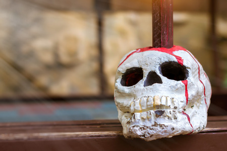 pierced: Skull is strung on a pole. Decorative artificial skull of a human head pierced with a spear, represents the backdrop for Halloween Stock Photo