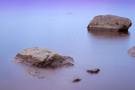 disappears: Stones on beach and huge rocks in calm water of Gulf of Vyborg. Evening calm in sea Bay, Leningrad region, Saint-Petersburg, Russia Stock Photo