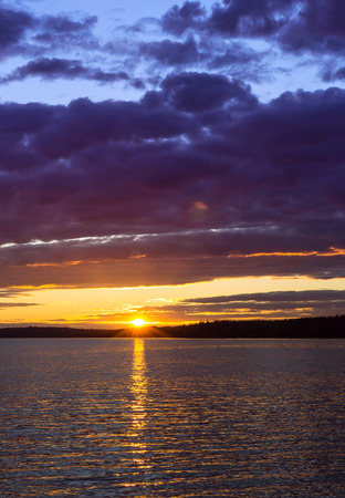 disappears: Vyborg. Bright summer sunset over Gulf of Vyborg. Evening calm in sea Bay, Leningrad region, Saint-Petersburg, Russia. Sun disappears behind the forest and reflected in water and clouds Stock Photo