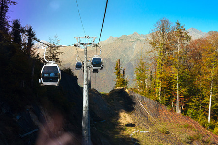 the olympic games: Mountain zipline through autumn forest on backdrop of Caucasus mountains, funicular railway to observation deck tops 2320 m. Krasnaya Polyana - Alpine ski resort, constructed from 2003 to 2011 for Sochi Olympic games. Rosa Khutor, Sochi, Russia