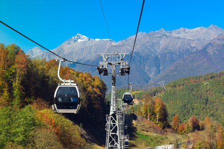 Mountain zipline through autumn forest on backdrop of Caucasus mountains, funicular railway to observation deck tops 2320 m. Krasnaya Polyana - Alpine ski resort, constructed from 2003 to 2011 for Sochi Olympic games. Rosa Khutor, Sochi, Russia