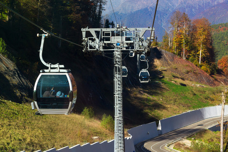 olympic games: Mountain zipline through autumn forest on backdrop of Caucasus mountains, funicular railway to observation deck tops 2320 m. Krasnaya Polyana - Alpine ski resort, constructed from 2003 to 2011 for Sochi Olympic games. Rosa Khutor, Sochi, Russia
