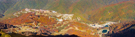 Ski resort with hotel and tourist infrastructure among the mountain massif. Autumn Caucasus mountain landscape, views of hills and peaks. Krasnaya Polyana - Alpine ski resort, constructed from 2003 to 2011 for Sochi games. Rosa Khutor, Sochi, Russia