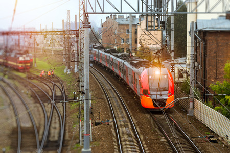 Modern electric locomotive pulling a high-speed train on rails. Technical railway operational locomotive depot on morning. Transport infrastructure of railways, route St. Petersburg - Moscow, Russia