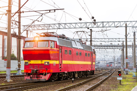 operational: Old electric locomotiv, rzd train rides on rails. Railroad tracks of technical railway station - operational locomotive depot. Transport infrastructure of Russian railways, St. Petersburg Stock Photo
