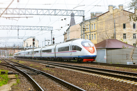 Modern hybrid electric locomotive Sapsan pulling high-speed train with railcars rzd on rails. Technical railway depot. Transport route St. Petersburg - Moscow, Saint-Petersburg railway station, Russia Stock Photo