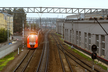 SAINT-PETERSBURG, RUSSIA - September 27, 2016: modern locomotive pulling a high-speed electric train Lastochka (Swallow) on rails. Technical railway station - operational locomotive depot on autumn morning in fog. Transport infrastructure of Russian Railw Editorial