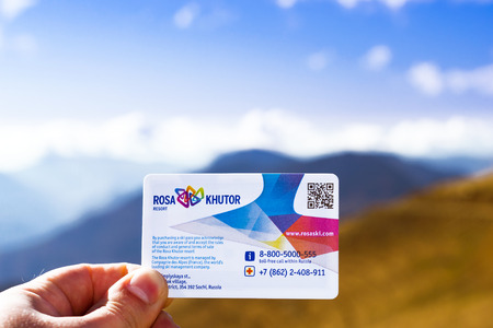 SOCHI, RUSSIA - OCTOBER 31, 2015: Card ski-pass for passage of funicular railway in hand on background of Caucasus mountains. Card-pass with scratch-stripe and bar-code. Rosa Khutor Alpine ski resort. Constructed from 2003 to 2011. Krasnaya Polyana, Sochi
