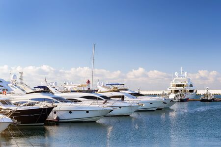 complex navigation: Luxury yachts and private boats moored at pier in Sochi seaport. In background the red warning lighthouse. Marine station complex Port. Krasnodarskiy kray, Russia