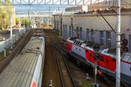 operational: Electric locomotive pulling high-speed train on rails. Technical railway station - operational locomotive depot. Transport infrastructure of Russian Railways, Saint-Petersburg