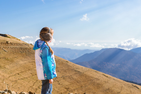 Girl with pigtail, dressed in jacket and warm fluffy headphones, admires of autumn mountain landscape, views of hills and peaks of Caucasus mountains. Krasnaya Polyana Alpine ski resort. Sochi, Russia