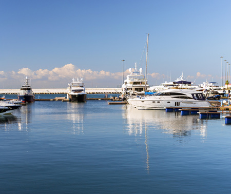 complex navigation: Luxury yachts and private boats moored at pier in Sochi seaport. In background is concrete promenade and Black sea. Marine station complex Port. Krasnodarskiy kray, Russia
