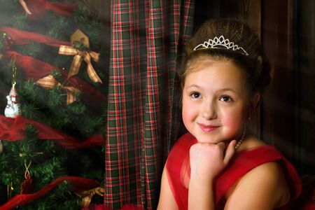 Winter Princess - pensive cute little teenage girl in red dress welcomes New year and Christmas in enchanting holiday interior with decorated Christmas tree