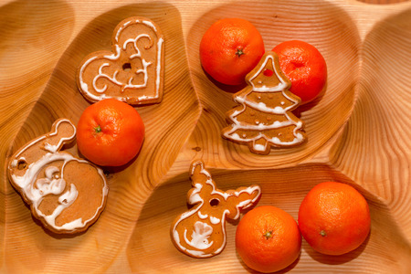 newyear: Christmas cookies and tangerines on wooden tray. New-year treats for holiday, gingerbread and citrus fruits lie on wood texture