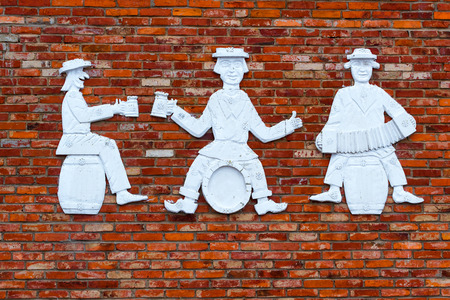 Stone figures of three men on brick wall. Humorous people are sitting on barrels, drinking beer and playing harmonica. Lithuanian provincial countryside. Baltic rustic sculpture. Griezpelkiai, Republic of Lithuania, European Union Stock Photo