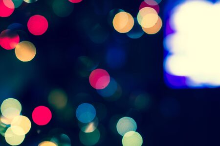 Festive New-year background with bokeh from Christmas tree lights glowing. Blurred colorful circles on dark holiday background