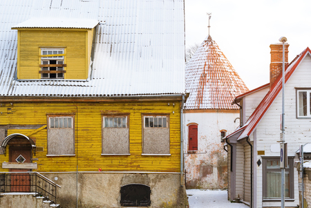 Parnu, Estonia January 10, 2016: Architectural diversity in centre of resort Estonian town Parnu. Historic white old tower in courtyard of old town. Snow-covered streets of tourist Baltic city in winter Stock Photo