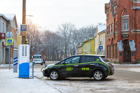 fueled: Parnu, Estonia - January 10, 2016: Electric-taxi brand Nissan fueled electric energy from eco-friendly high-tech charging battery station. Modern technologies of ecological transportation. National Estonian architecture on snowy winter street Editorial