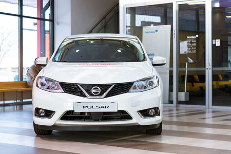 showpiece: Parnu, Estonia - January 10, 2016: Nissan Pulsar in the lobby of the shopping centre Port Artur 2. New white Japanese car as a showpiece. Stylish family vehicle at the exhibition car dealer Editorial