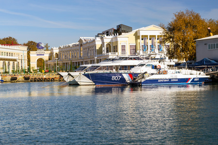 sea port: Sochi, Russia - November 1, 2015: Rescue and border guard motorboat moored at pier in Sochi seaport. In background the shopping gallery Grand Marina. Marine station complex Port. Krasnodarskiy kray, Russia Editorial