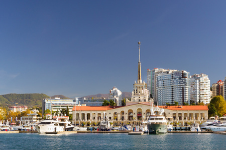 complex navigation: Sochi, Russia - November 1, 2015: View from water at Sochi sea port. Luxury yachts and private boats moored at pier. In background architecture modern resort town, hotels and sanatoriums. Marine station complex Port. Krasnodarskiy kray, Russia